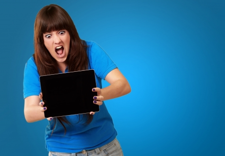 devastated: Woman Holding touchpad Isolated On Blue Background