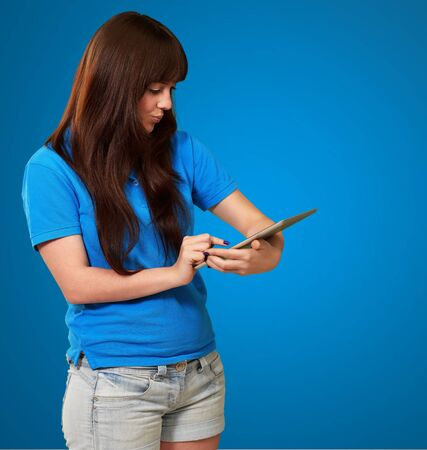 Woman Using Ipad Isolated On Blue Background photo
