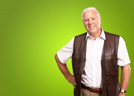 1 senior: Hombre mayor que se coloca con la mano en la cadera en el fondo verde