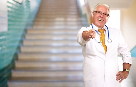 Portrait Of A Senior Doctor Pointing, Indoor photo