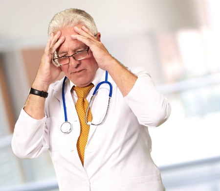 Portrait Of A Senior Doctor Holding His Head, Background photo