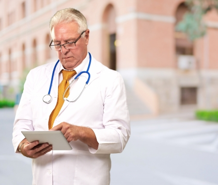 Portrait Of A Male Doctor Holding A Tab, Outdoor photo