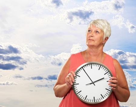 looking at watch: Senior Woman Holding A Clock, Outdoor