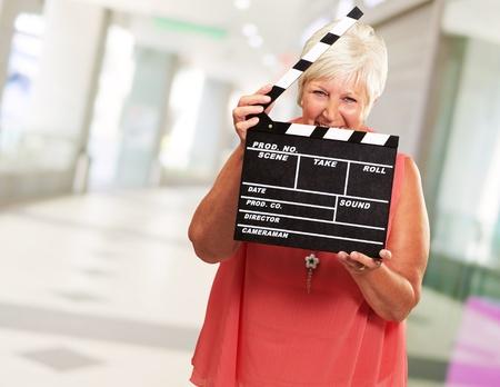 western script: Senior Woman Holding Clapper, Indoor