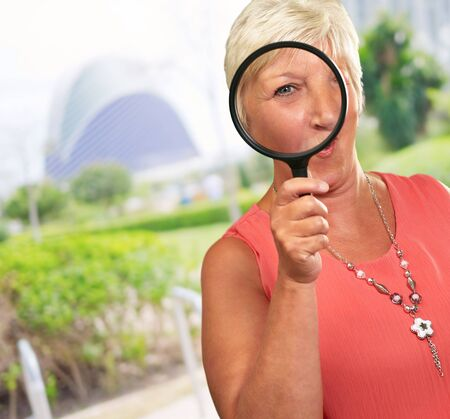 funny glasses: Senior Woman Looking Through A Magnifying Glass, Outdoor Stock Photo