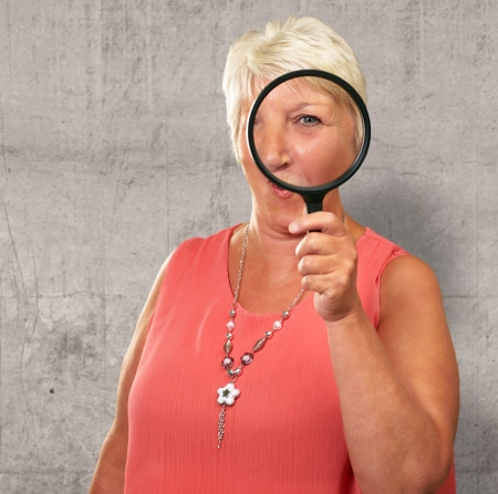 Senior Woman Looking Through A Magnifying, Indoor photo