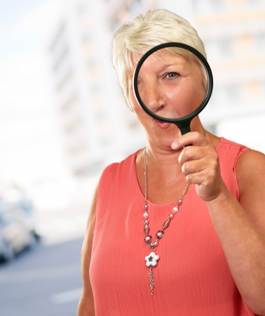 Senior Woman Looking Through A Magnifying, Outdoor photo