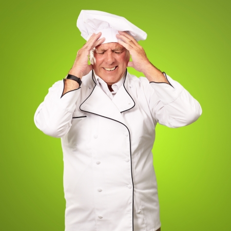 profess: Portrait Of Chef With Painfully Head On Green Background