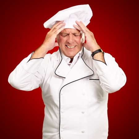 painfully: Portrait Of Chef With Painfully Head On Red Background