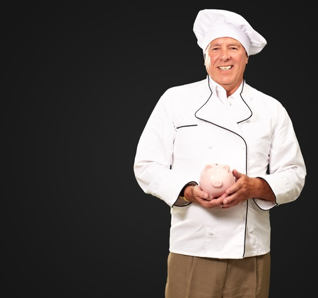 Portrait Of A Chef Holding Piggy Bank Isolated On Black Background photo
