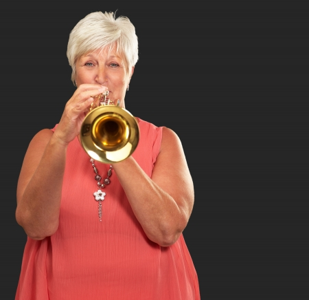 Mature Woman Blowing Her Trumpet Isolated On Black Background photo