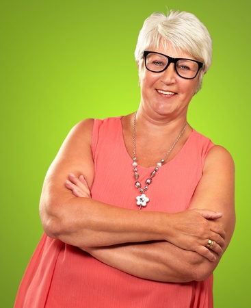 folded hands: Senior Woman With Hands Folded Isolated On Green Background