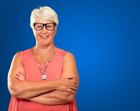 damas antiguas: Mujer mayor con los brazos cruzados aislados sobre fondo azul