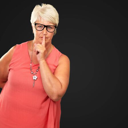 Senior Woman With Finger On Lips Isolated On Black Background Stock Photo - 16039327