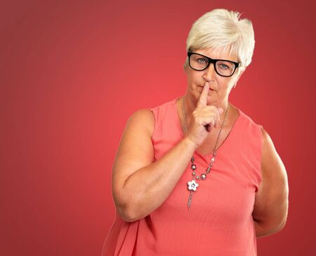 hushed: Senior Woman With Finger On Lips Isolated On Pink Background