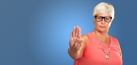 banned: Portrait Of A Senior Woman Showing Stop Sign On Blue Background Stock Photo