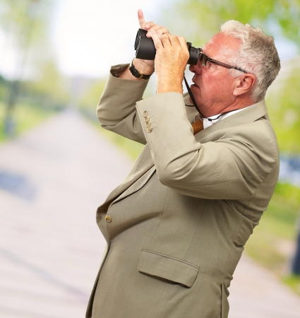 Senior Man Looking Through Binoculars, Outdoor photo