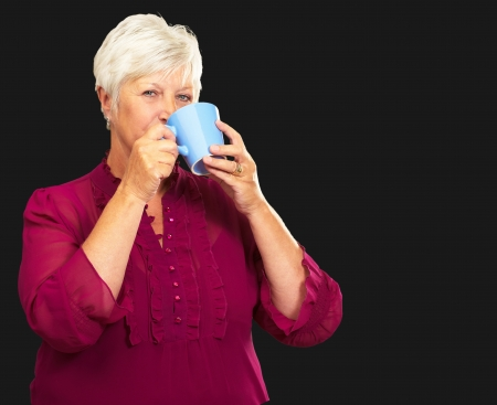 Senior Woman Drinking From Cup Isolated On Black Background photo