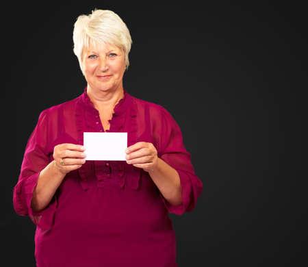 Senior Woman Holding A Card On Black Background photo