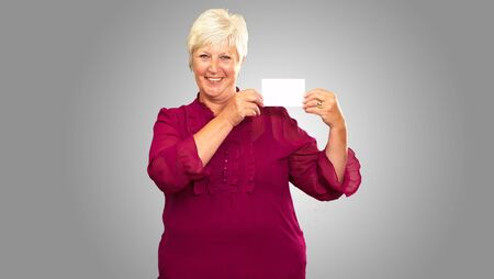 Senior Woman Holding A Card On gray Background photo