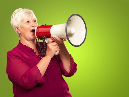 Portrait Of A Senior Woman With Megaphone On Green Background photo