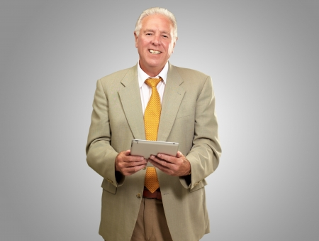 Portrait Of A Senior Man Holding A Laptop On Gray Background photo