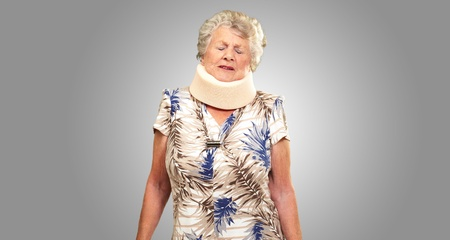 A Senior Woman Wearing A Neckbrace On gray Background photo