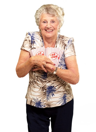 Portrait Of A Senior Woman Holding Popcorn Box On White Background photo