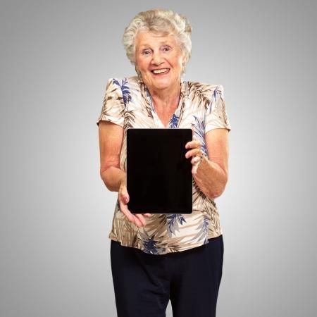 Portret Van Een Senior Vrouw Met Een Digitale Tablet op grijze achtergrond