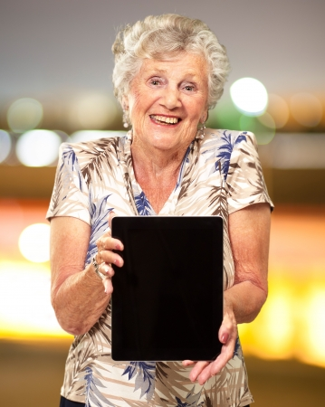 Portrait Of A Senior Woman Holding A Digital Tablet, Outdoor Stock Photo