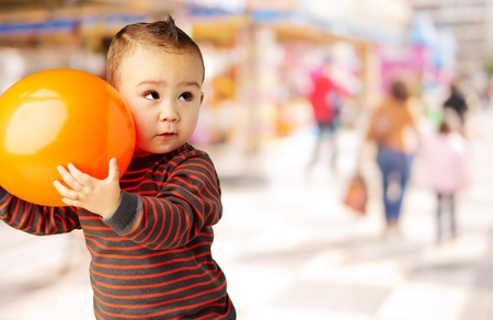 kid holding a orange balloon at mall photo
