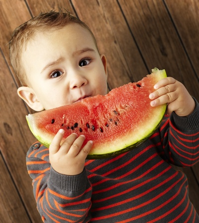 portrait of a handsome kid holding a watermelon against a wooden background photo