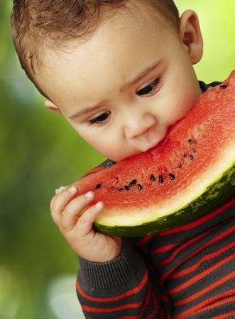 portrait of a handsome kid holding a watermelon piece and tasting it against a nature background photo
