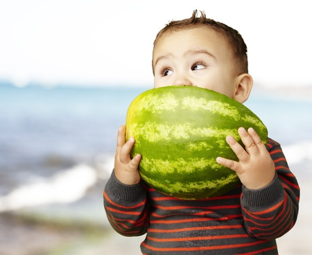 portrait of a handsome kid holding a watermelon and eating it against a sea background photo