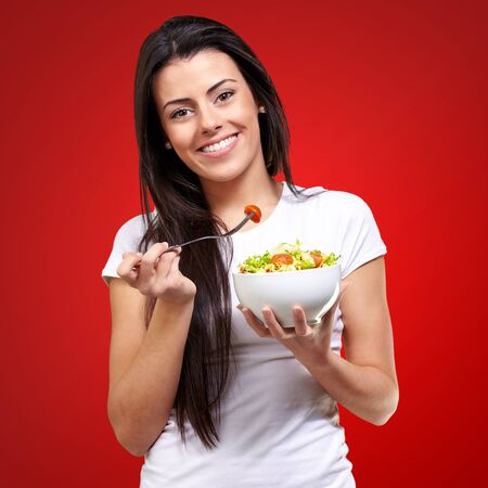 portrait of healthy woman eating salad against a red background Stock Photo - 16140078