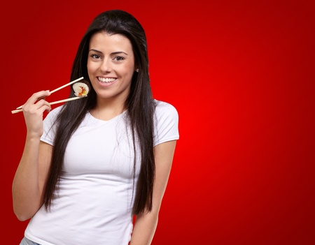 Portrait Of A Female Holding A Maki Sushi On Red Background photo