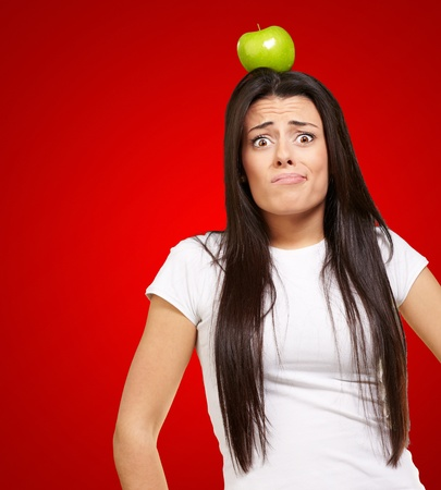 portrait of young woman holding green apple on her head over red photo
