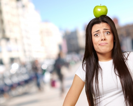 portrait of young woman holding green apple on her head at crowded city photo