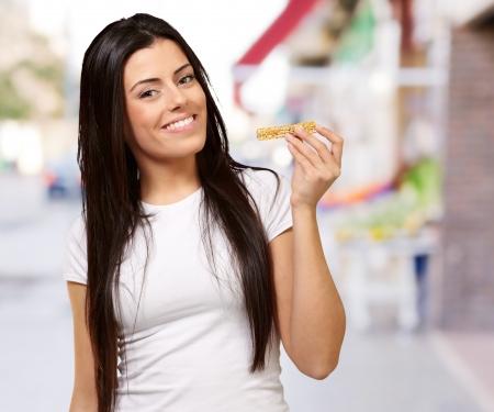 barra de cereal: Retrato de mujer joven comiendo barra de cereal en la calle