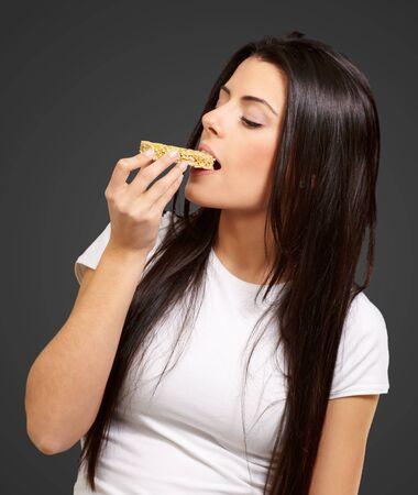 barra de cereal: Young Girl Eating Cereal Bar Aislados En Fondo Negro