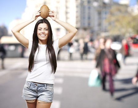 young girl holding a coconut on her head against a street background photo