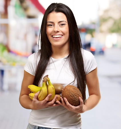 portrait of young woman holding tropical fruits at street photo