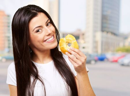 portrait of young woman eating a donut at big city Stock Photo - 16252209