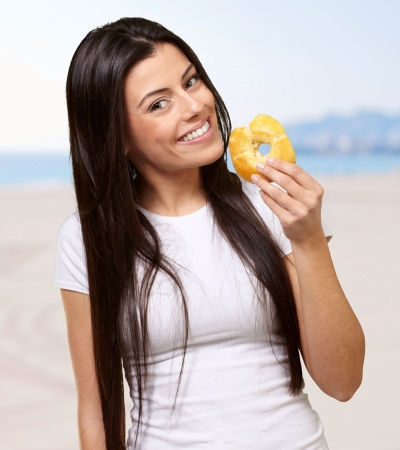 portrait of young woman holding donut against the beach photo