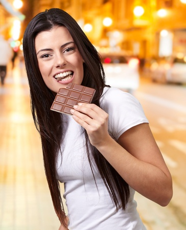 portrait of young woman eating chocolate bar at night city photo