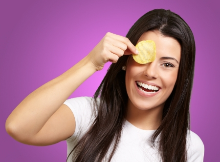 portrait of young woman holding a potato chip in front of her eye over purple photo