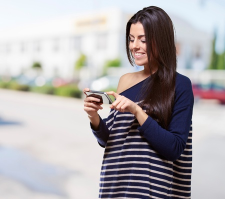 portrait of young woman touching a modern mobile at street