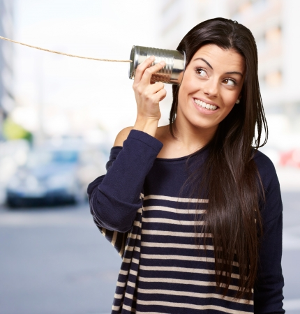 Young woman hearing using a metal tin can at city Stock Photo - 16252260