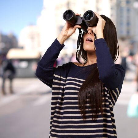 lejos: retrato de una niña pequeña mirando a través de binoculares en una ciudad