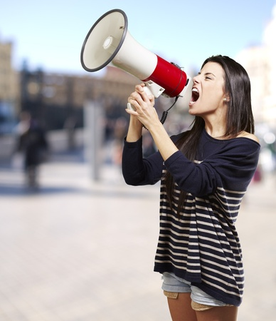 young woman shouting with a megaphone against a street background Stock Photo - 16252278